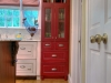 Red cabinetry stands out against the white